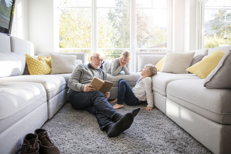 Grandfather reading to grandkids in a gray living room.