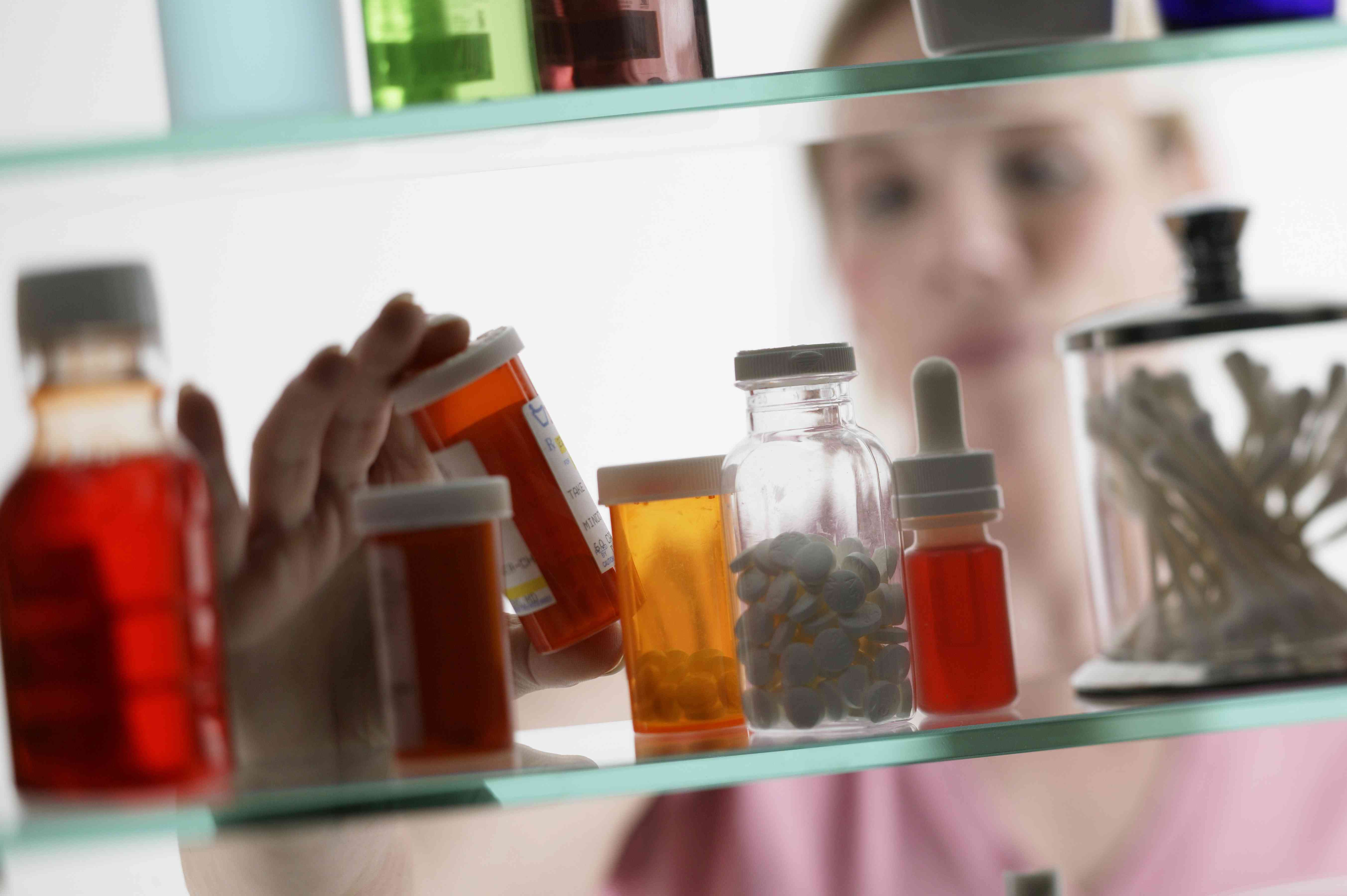 person taking pills from medicine cabinet