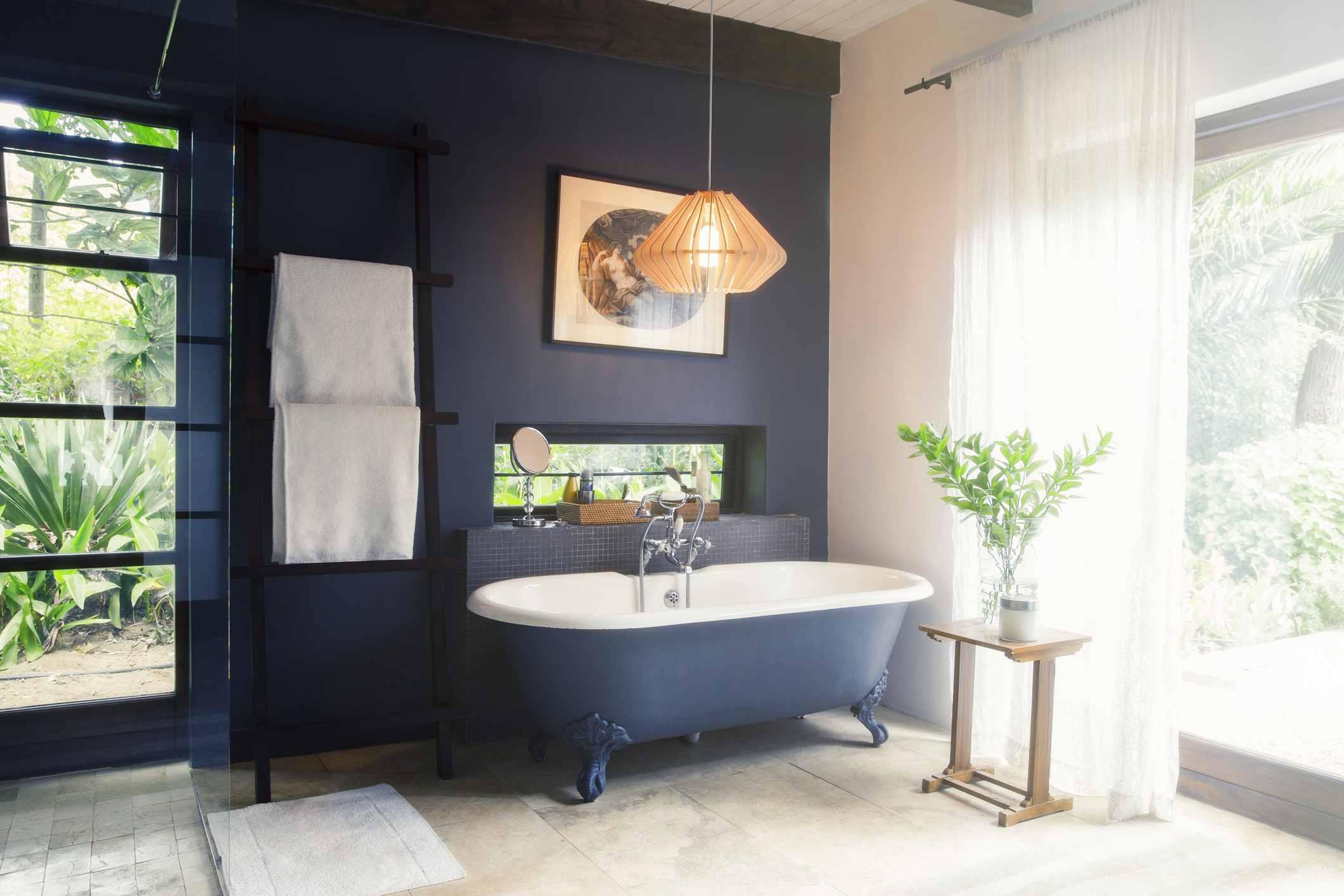 A dark blue bathroom with a bathtub and towel rack with a beautiful backyard view