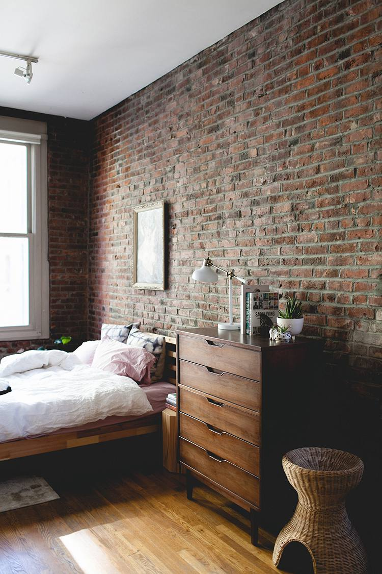 bedroom with exposed brick and a mid century dresser