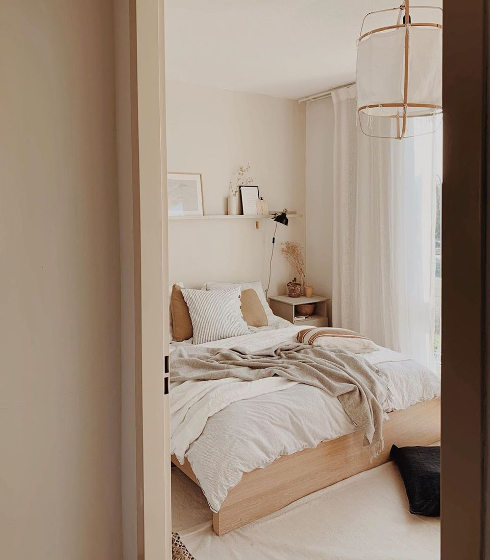 Bedroom with light colors and wooden furniture