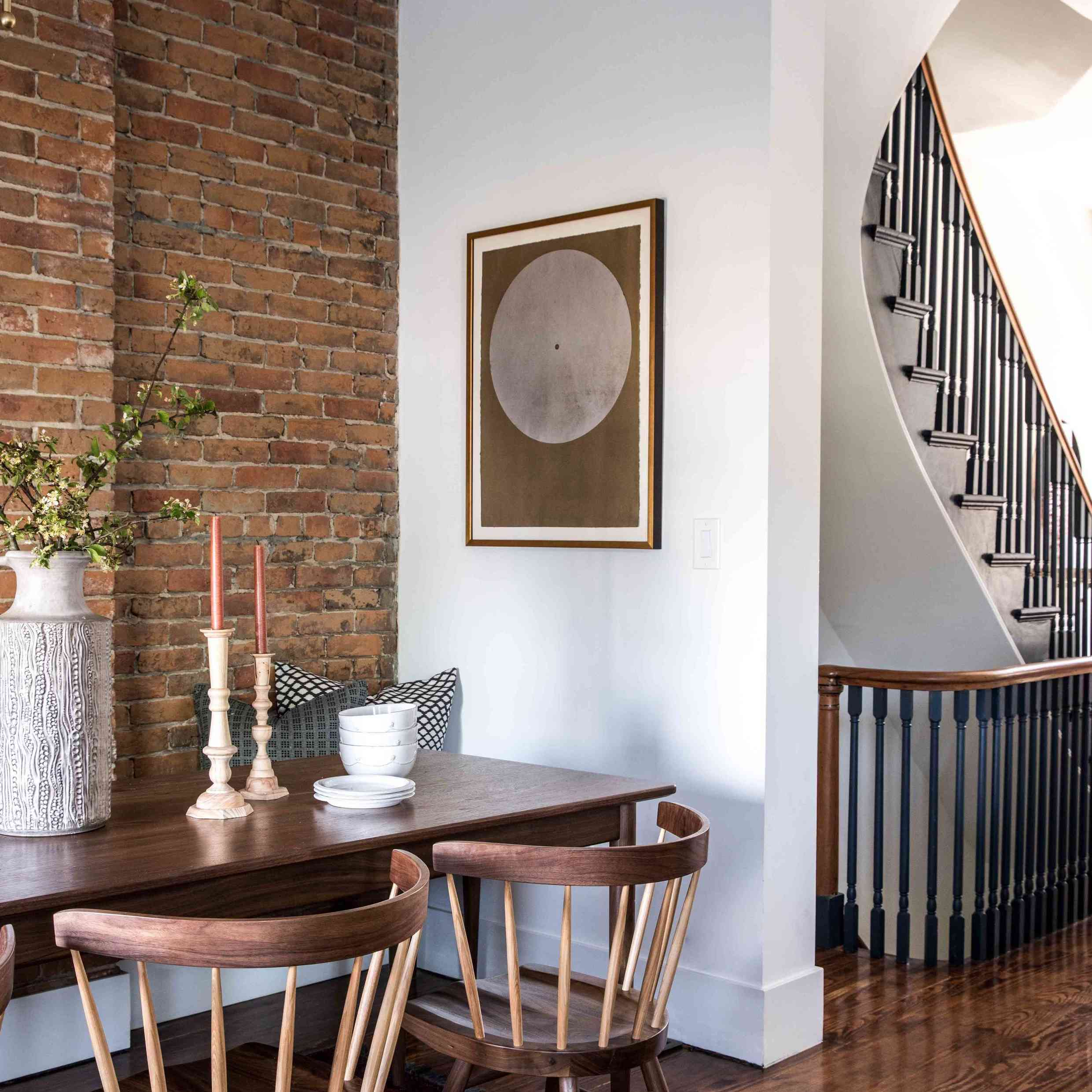 dining room with exposed brick wall and white wall corner, lone piece of artwork hanging