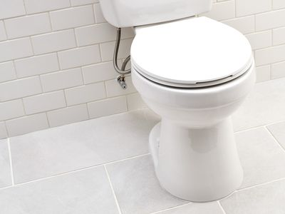 White toilet in bathroom with white and gray tiles and flange extender