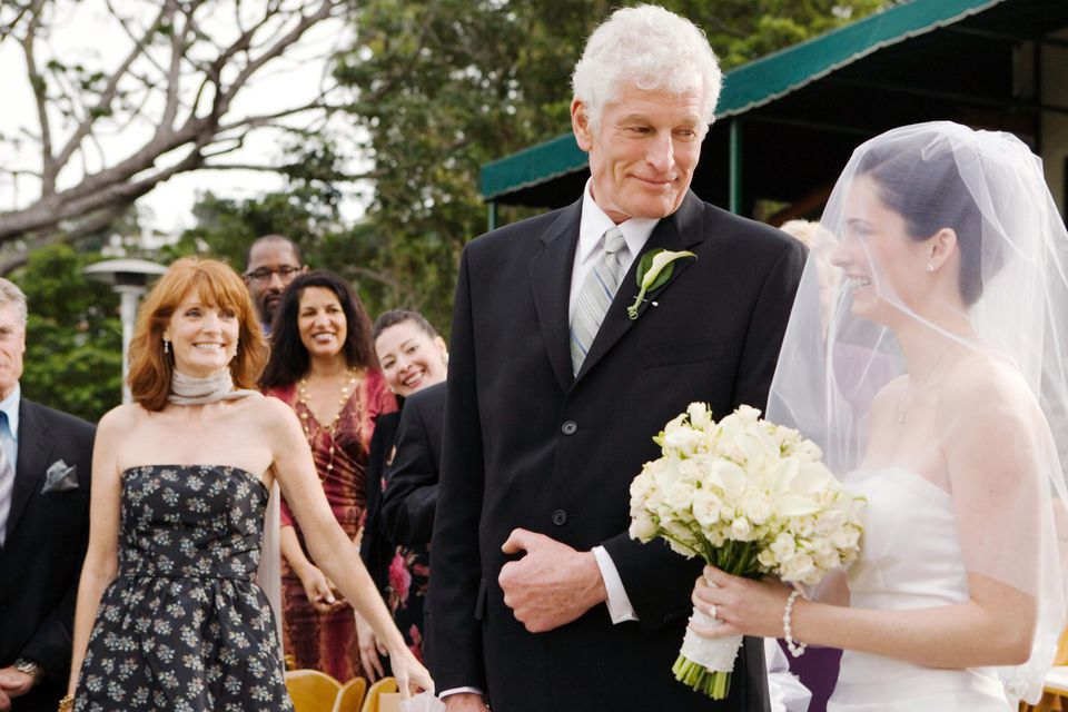 Bride walking down aisle with father, wedding guests watching