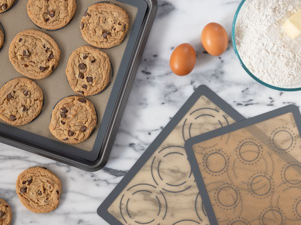 Silicone baking mats next to baked cookies and baking ingredients