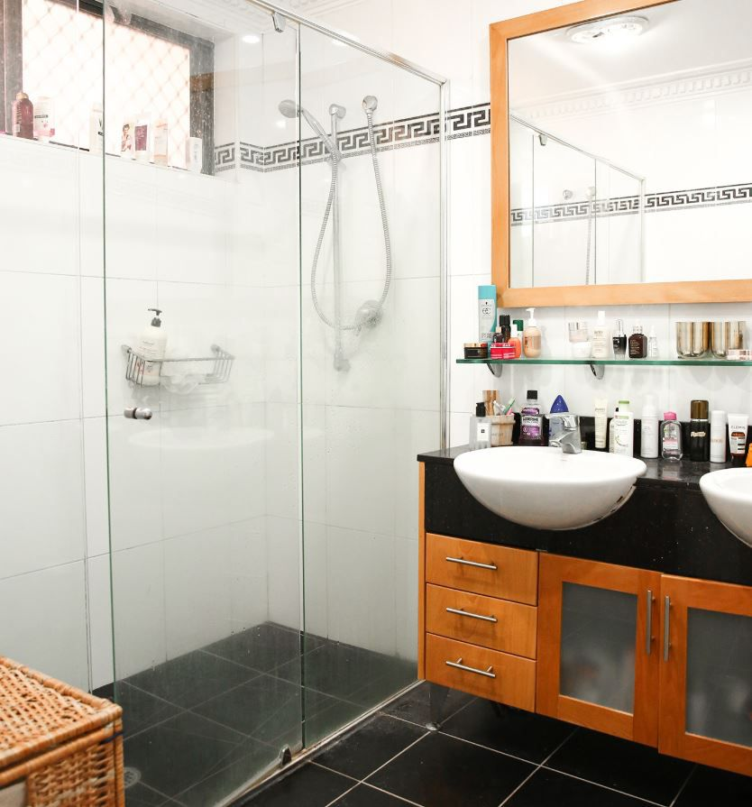 Bathroom with black tile floor and outdated fixtures.