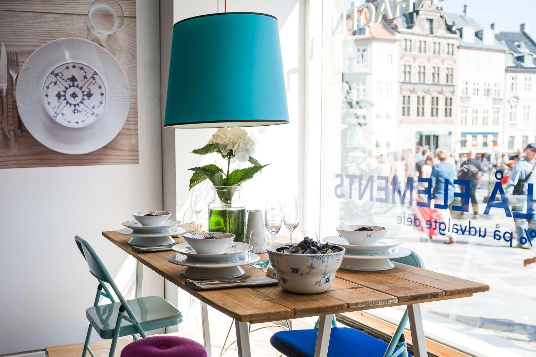 Mesa puesta cerca de la ventana de una tienda con pantalla de lámpara azul sobre la mesa de arriba