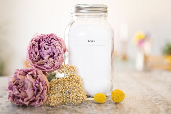 Dried pink and yellow flowers next to glass jar of borax