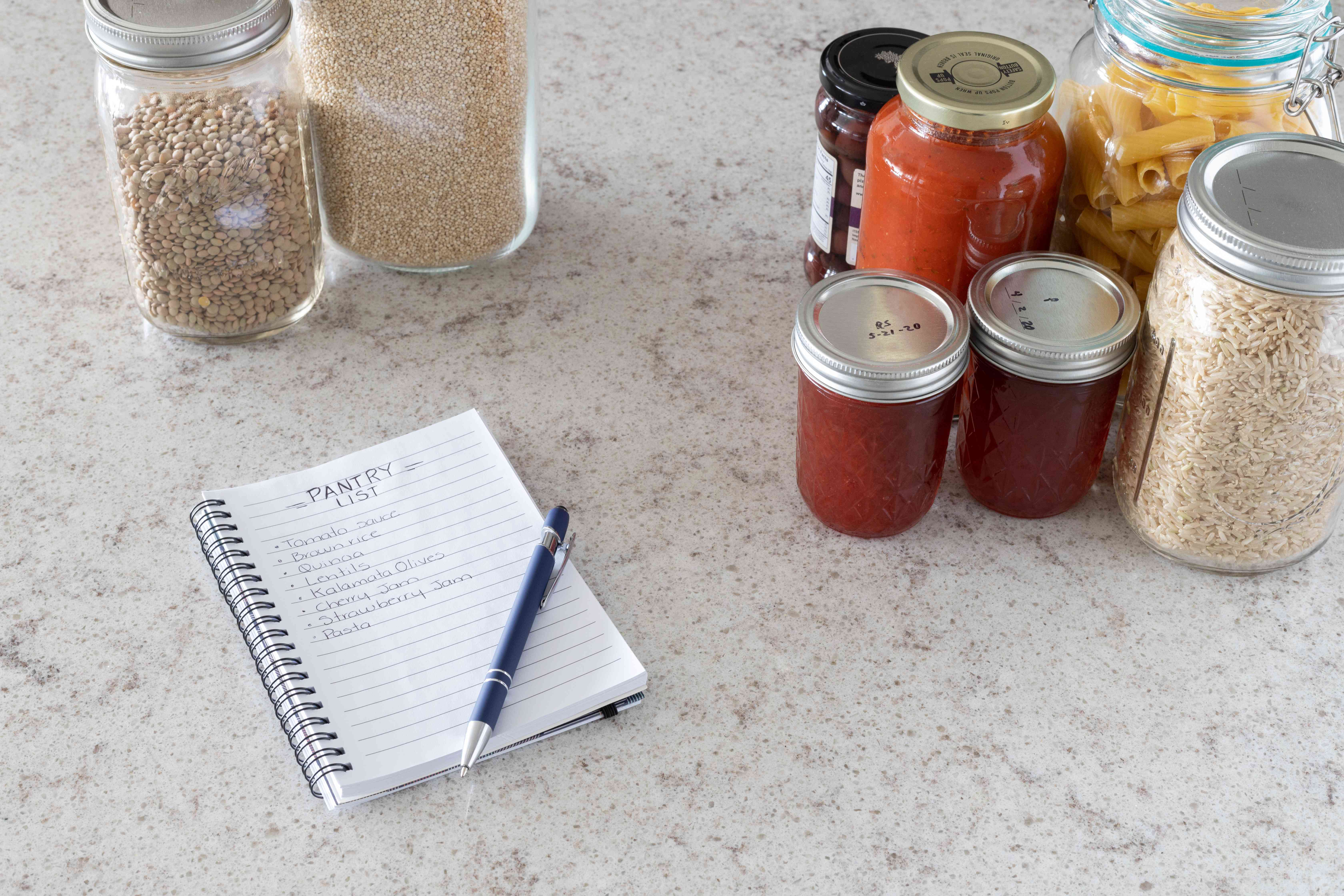 Paper pad with list and pen on top next to kitchen items on marbled countertop