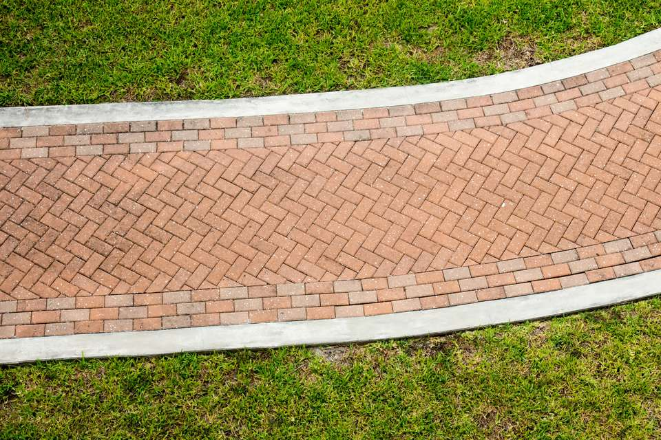 Red brick pattern sidewalk through grass