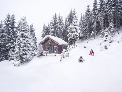 Austria, Altenmarkt-Zauchensee, family tobogganing at wooden house at Christmas time