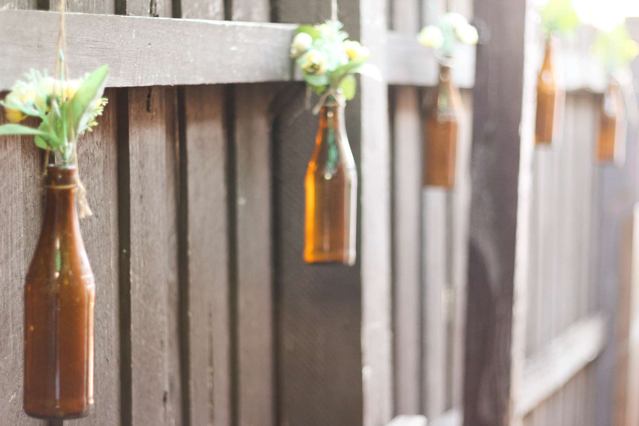 Glass bottles filled with blooms hanging from a wood fence