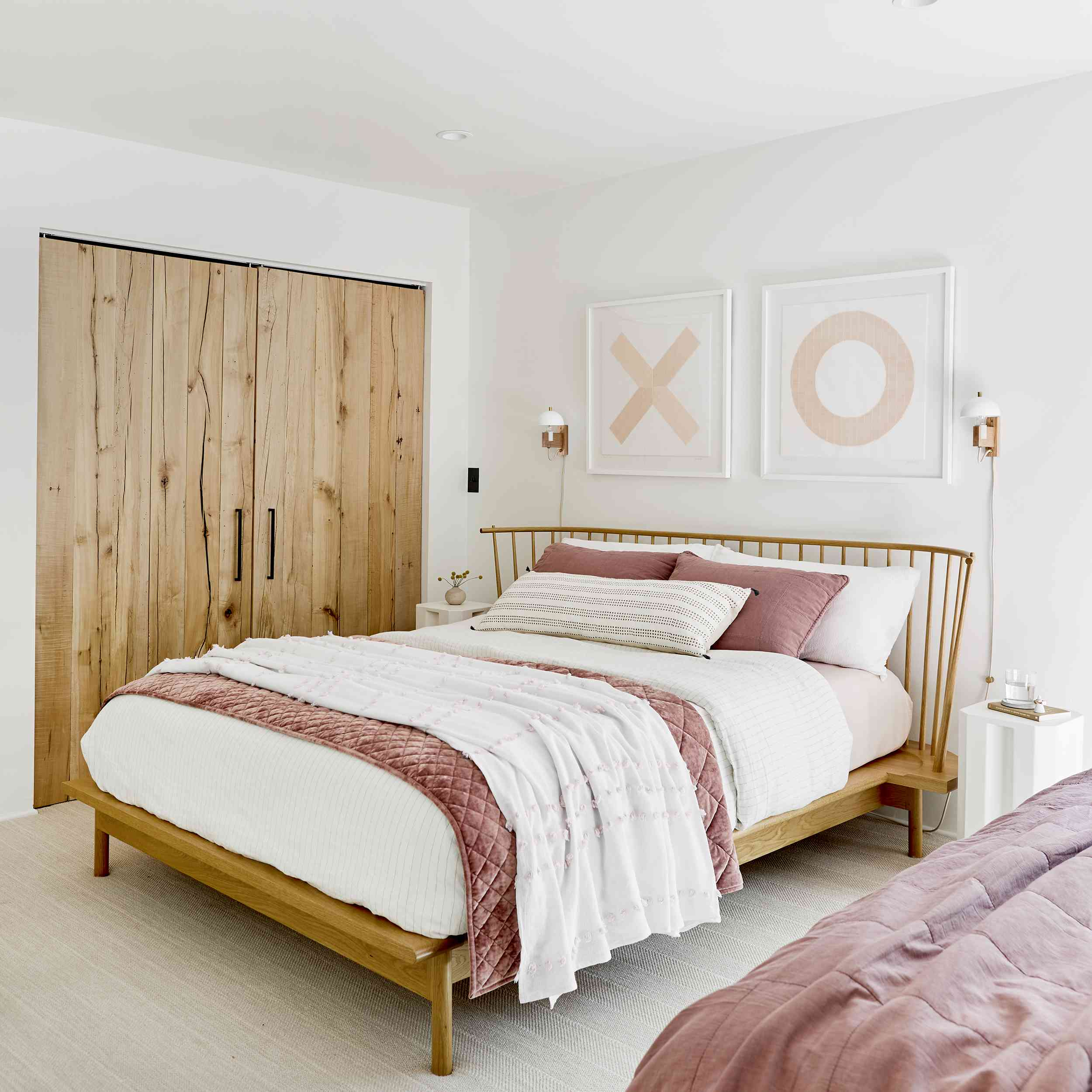 White and dusty pink bedroom with XO wall art and a wooden door