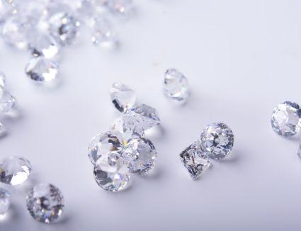 Diamond with tweezers and magnifier.Gemstone Beauty.Luxury satin background. Wedding style.