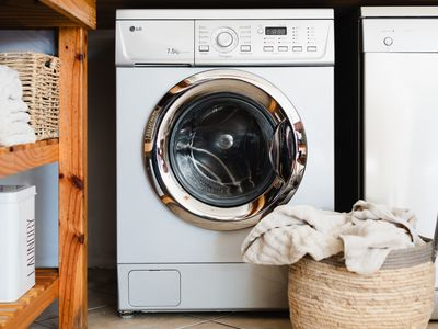 Washing machine next to basket with a pile of towels and wood shelving with laundry materials