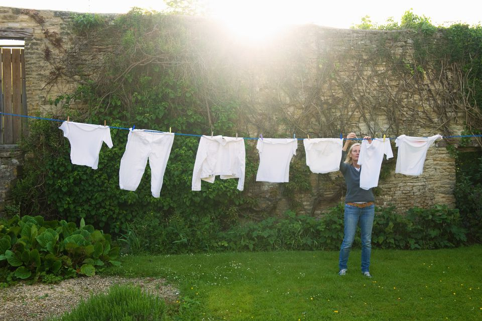 Woman hanging white laundry