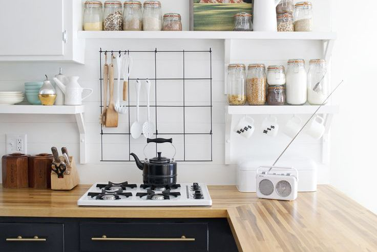 Wire fence with utensils hung above a stove in a kitchen