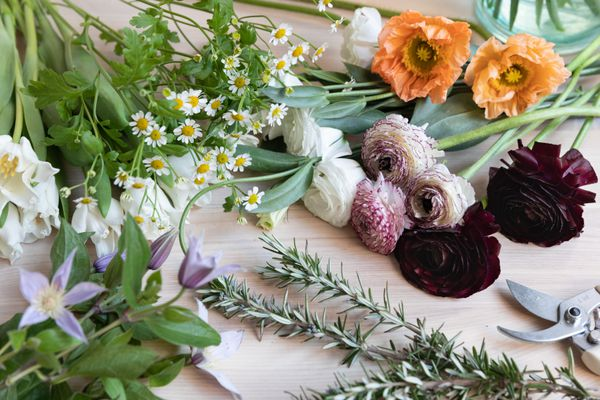 Variety of flowers laid on wooden surface for bouquet arrangement