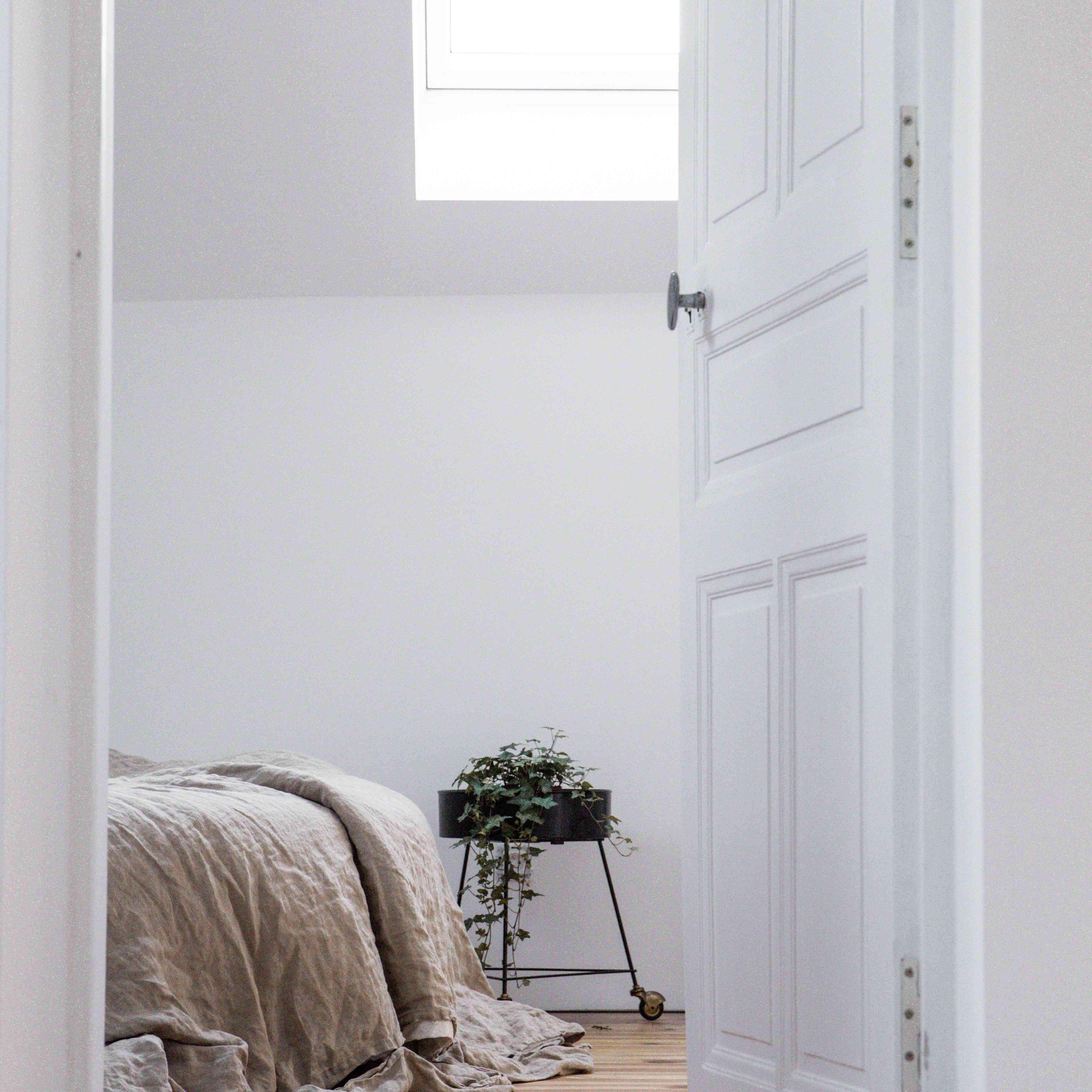 looking into a white bedroom through the door
