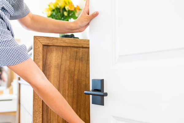 White door that sticks being fixed with hands