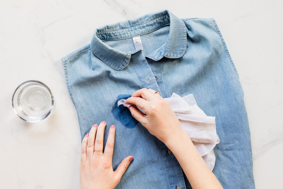person dabbing a damp cloth on a garment