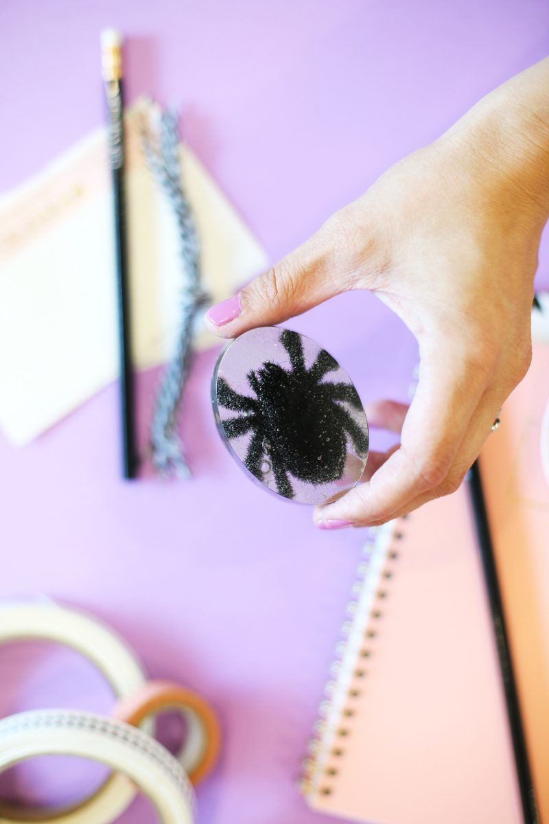 A woman holding a spider paperweight