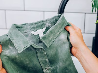 White mildew stains on green colored shirt held up
