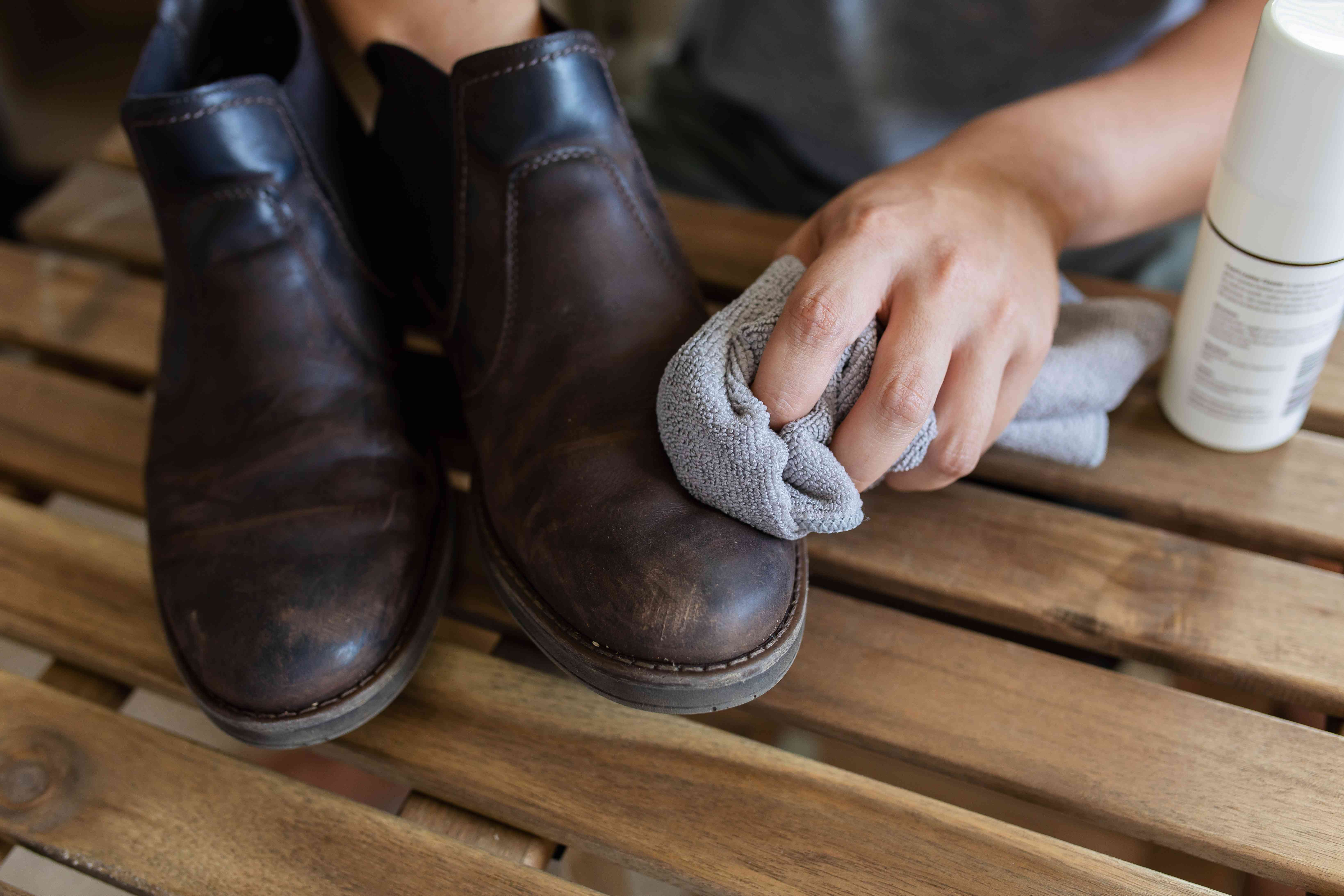person cleaning leather boots