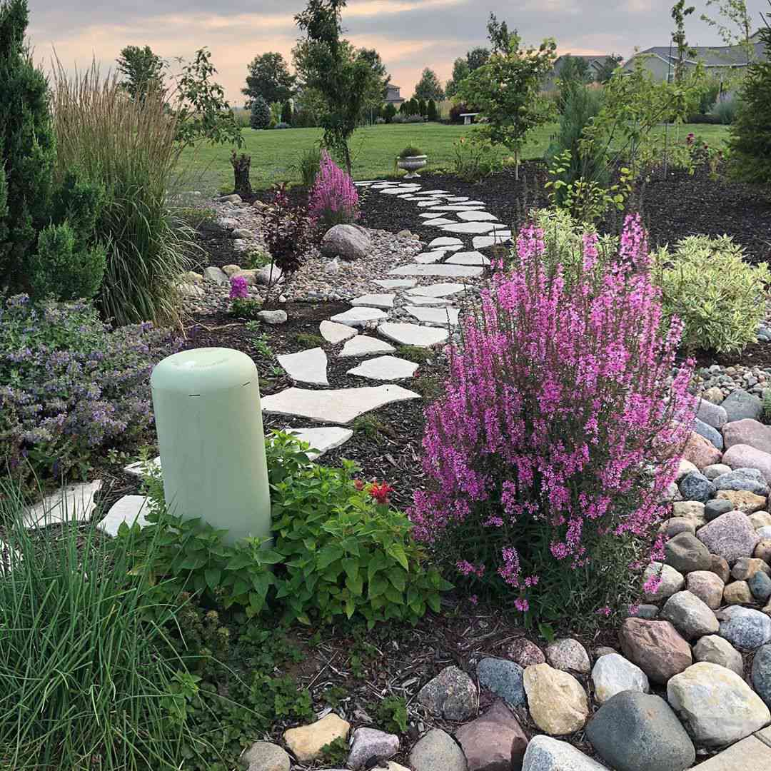 Garden with natural slate paving stones and river rocks.