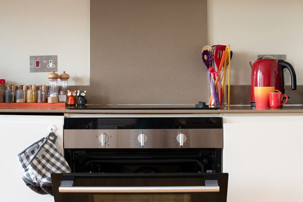 View of a kitchen worktop and oven with spices and utensils