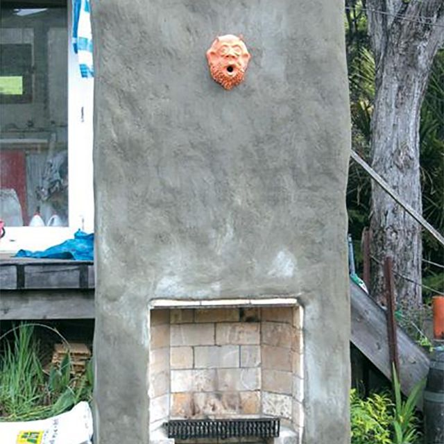 An outdoor fireplace with a gargoyle