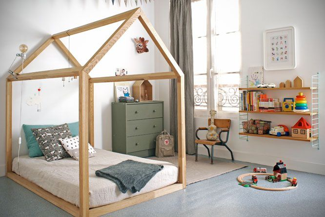 A house-framed floor bed in a Montessori-inspired toddler room with a shelf of toys.