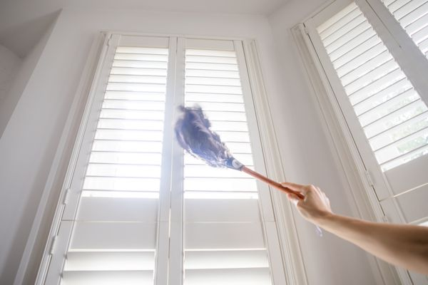 Dusting shutters with a feather duster