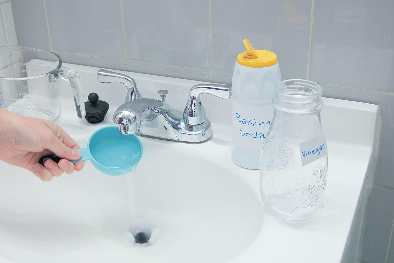 person pouring vinegar down a drain