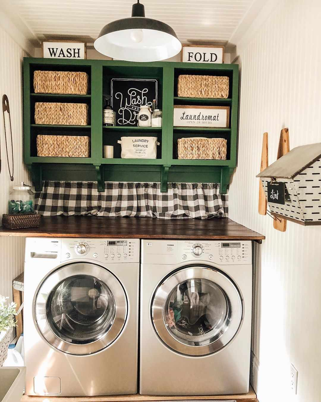 Small laundry room with green shelves