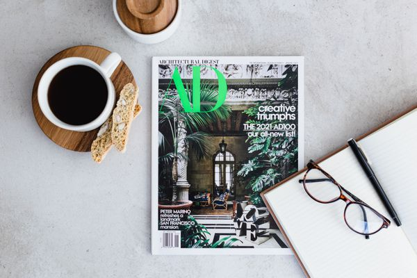 Architectual Digest home decorating magazine in middle of table with coffee cup and open notebook