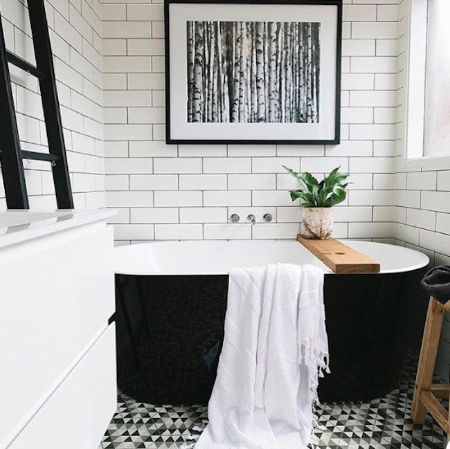 Bathroom with black tub and white tile on the wall.