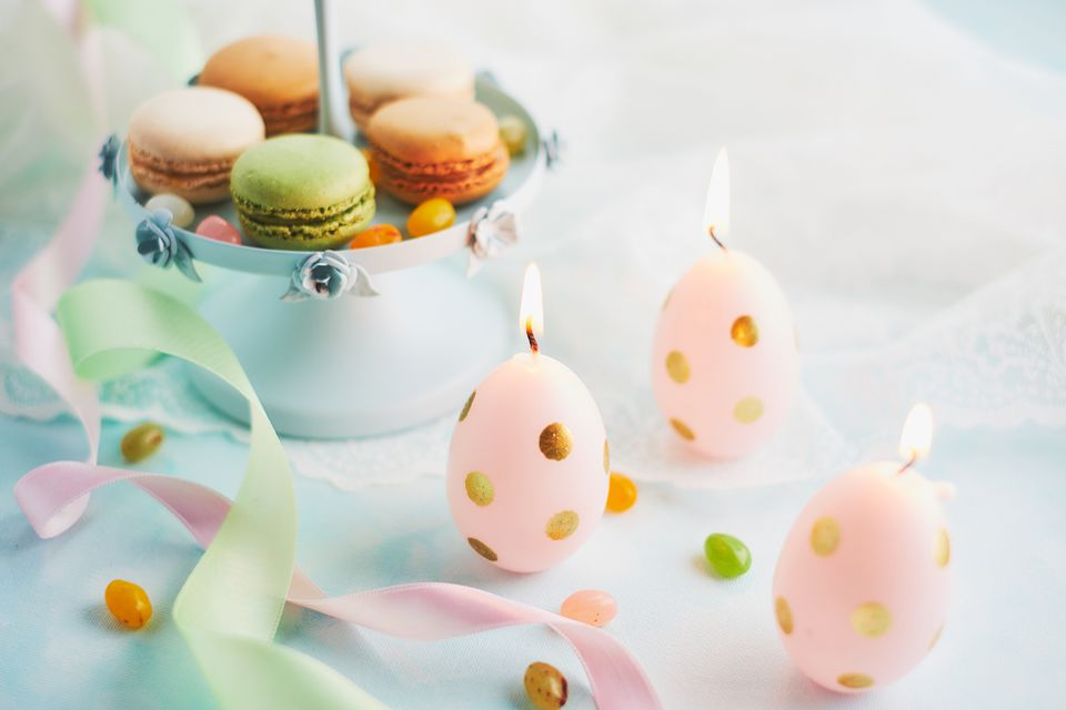 Macaroon and easter egg candles on table