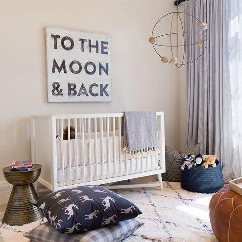 Minimalist nursery with neutral colors including a sign that reads To the Moon & Back.
