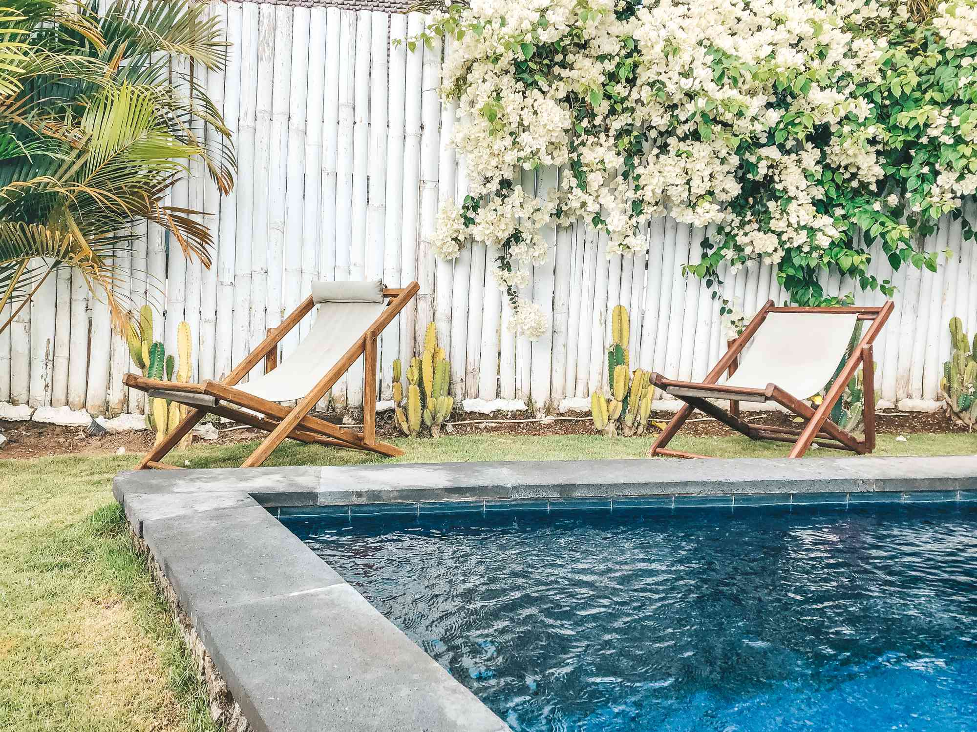 A backyard pool surrounded by a white bamboo fence and lounge chairs.