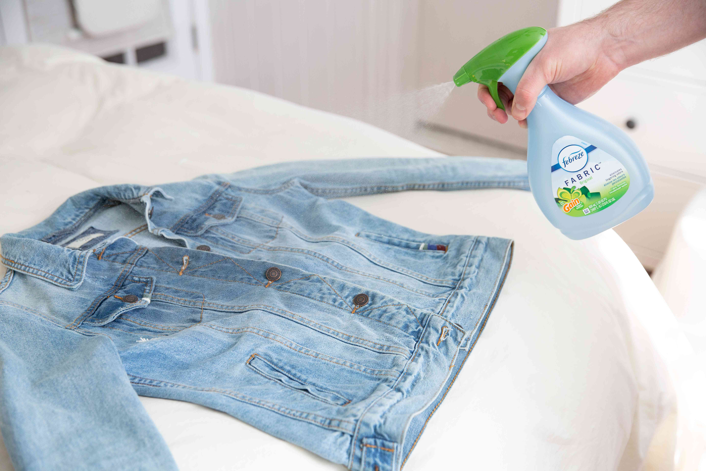 spraying a jacket with Febreze
