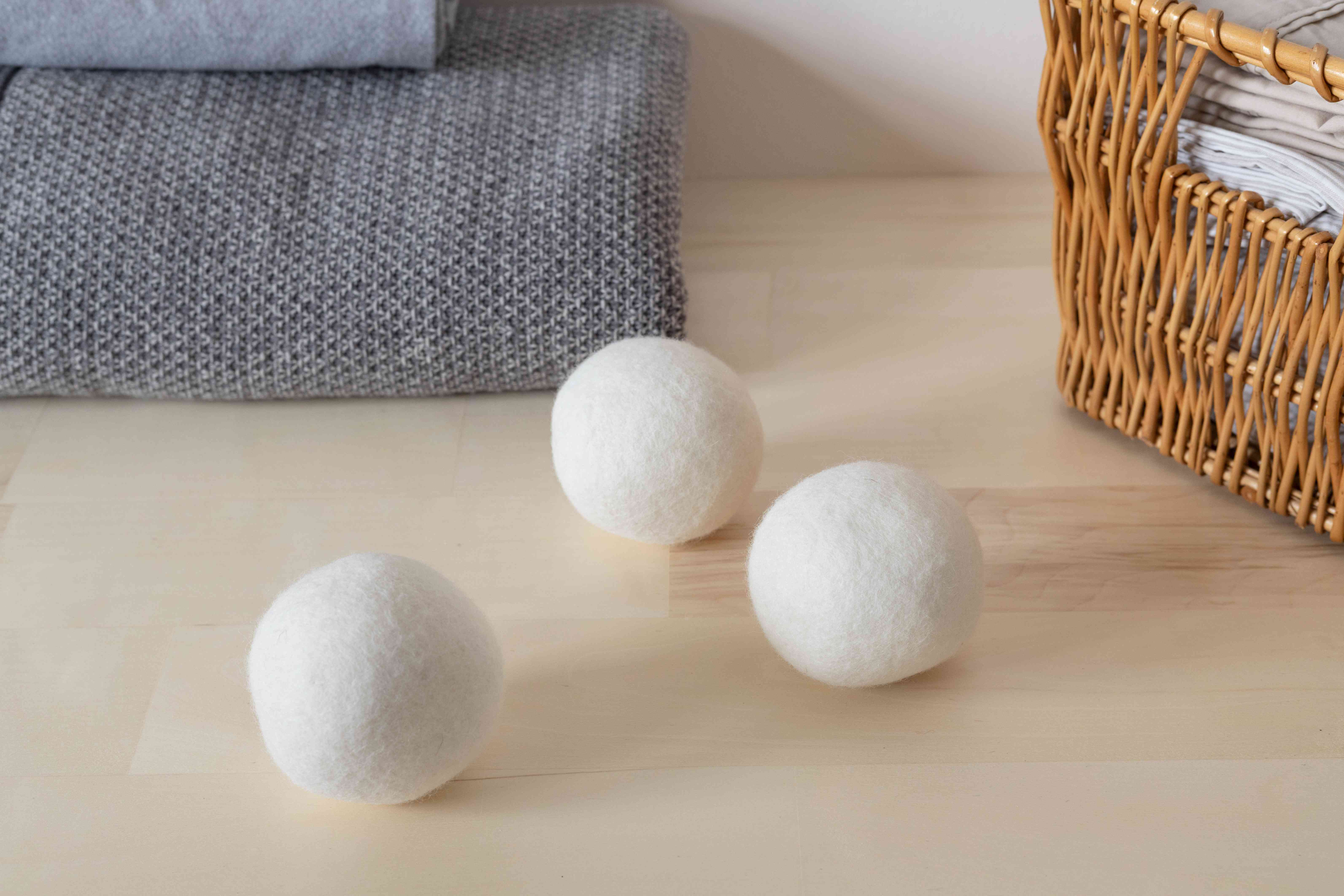 Dryer balls next to folded clothing and wicker basket