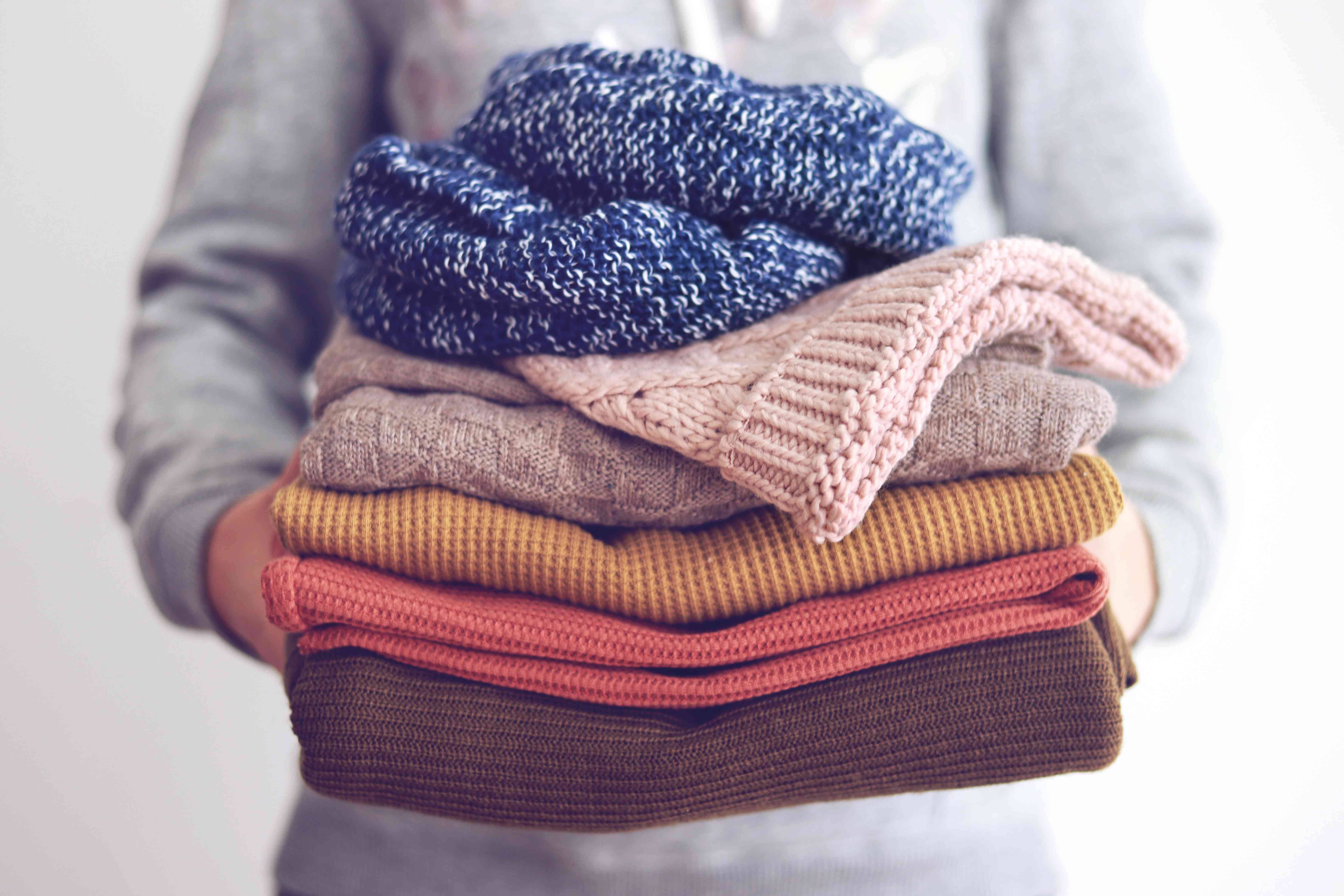 person holding a stack of sweaters