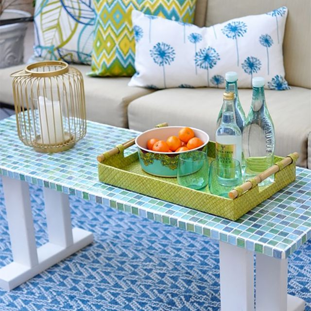 A white mosaic table outside next to a couch
