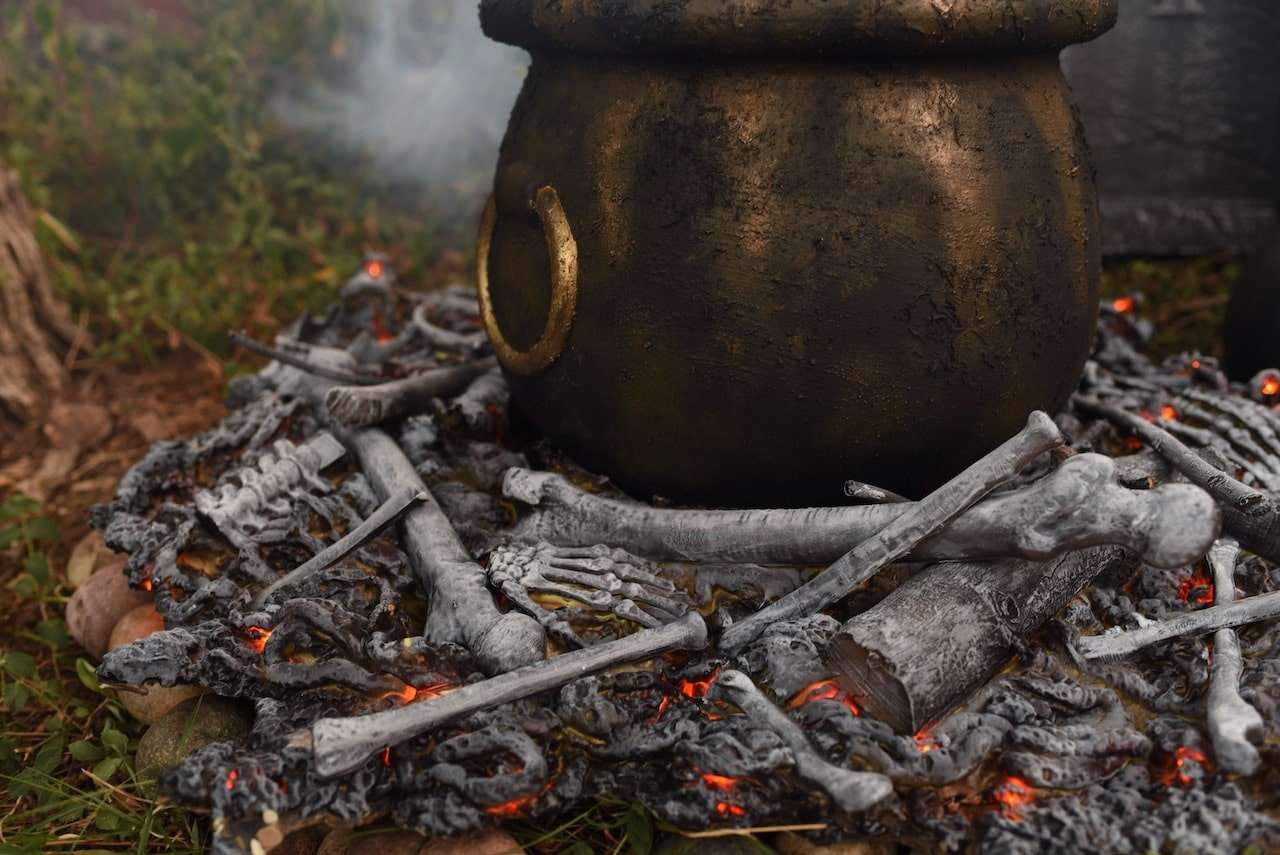 A cauldron with bones on a fire