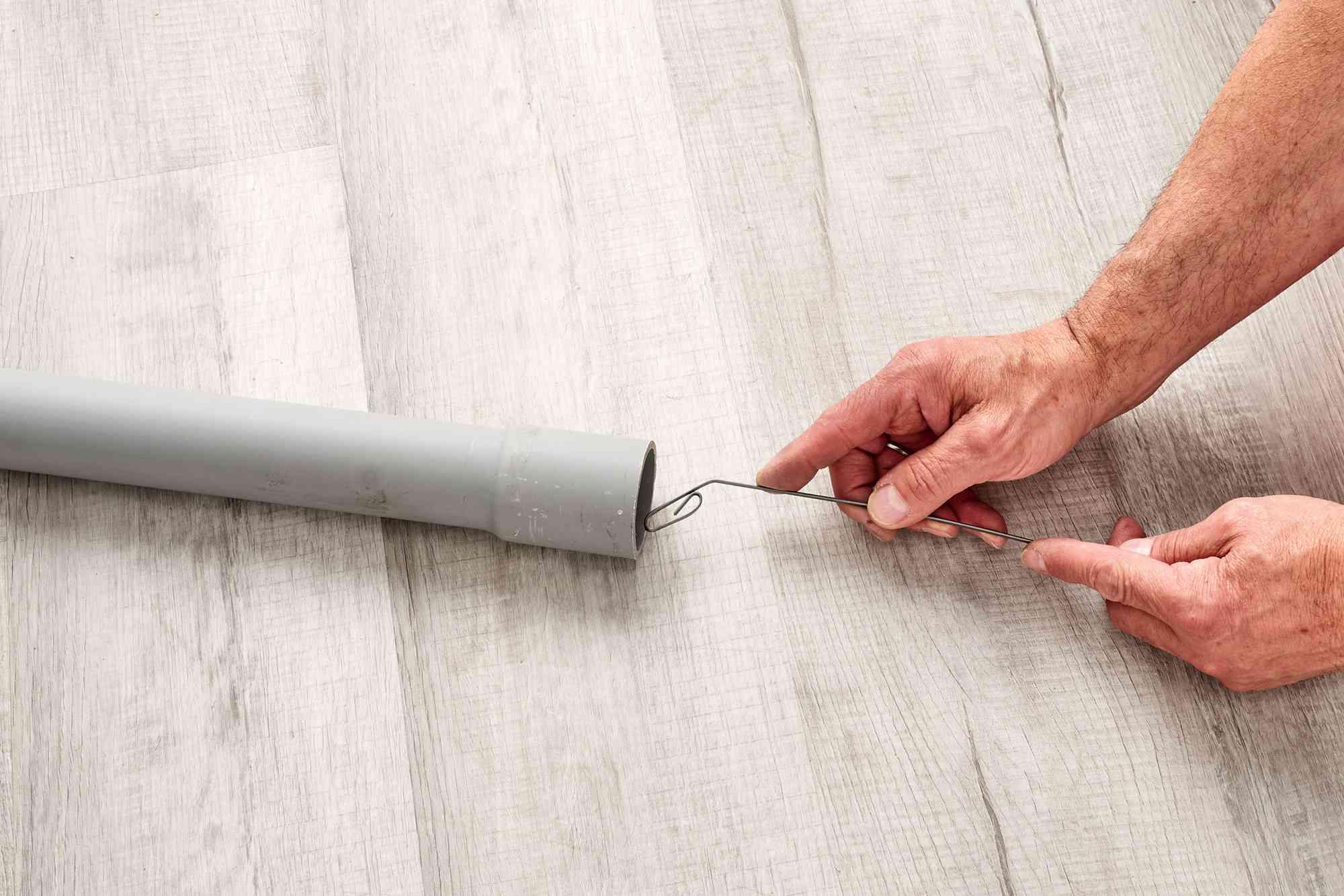 Fish tape end fed through conduit tube