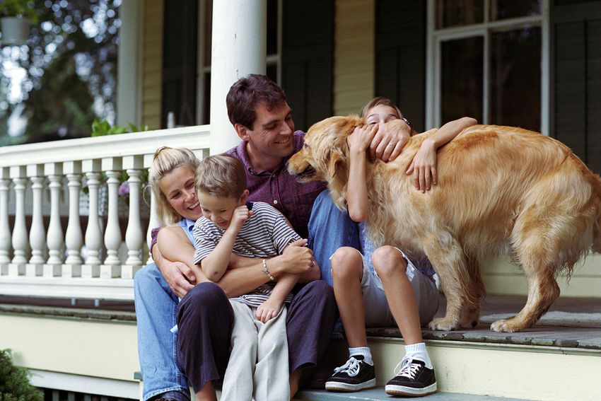 Family with a dog in front of their house
