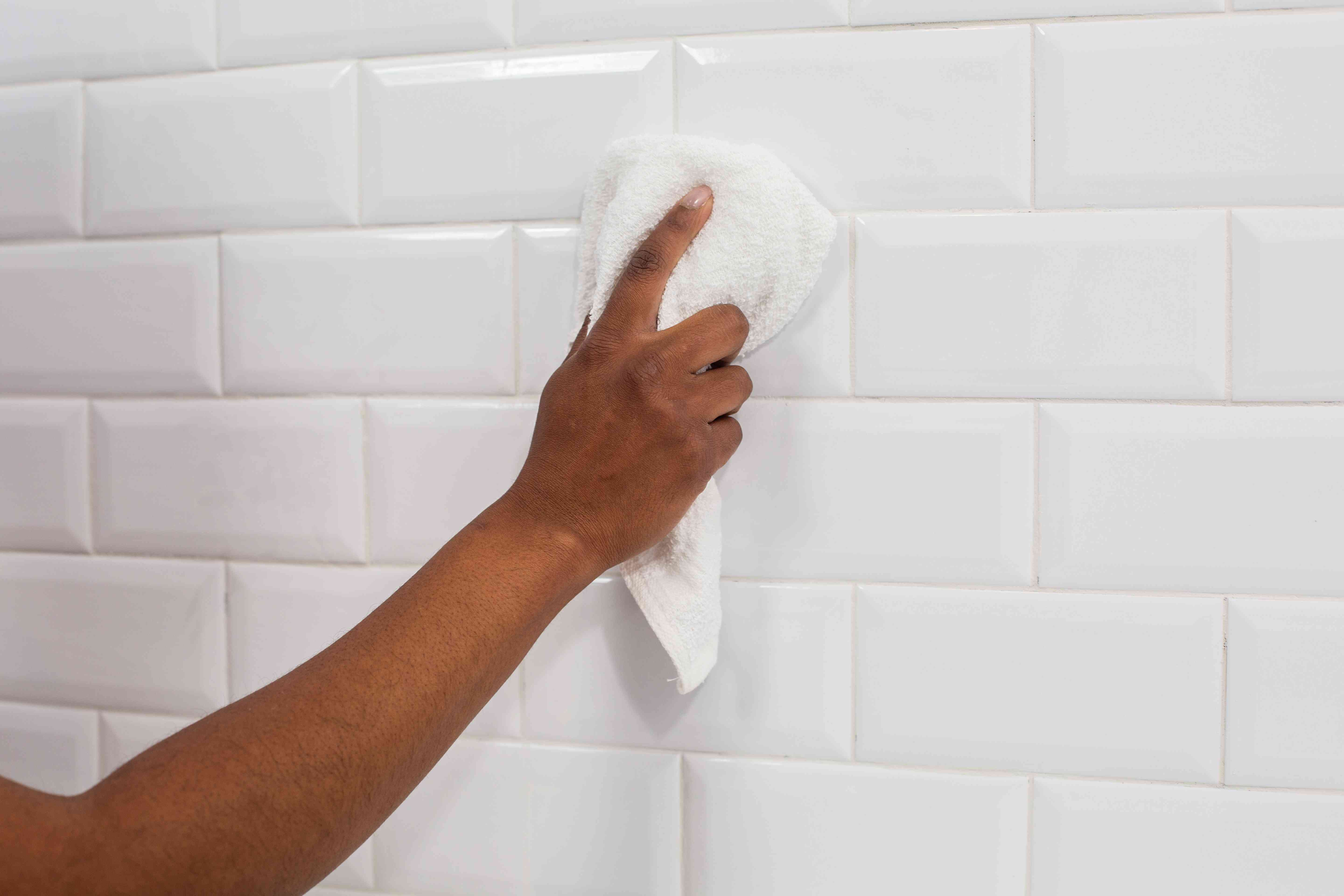White ceramic wall tile cleaning haze with white towel