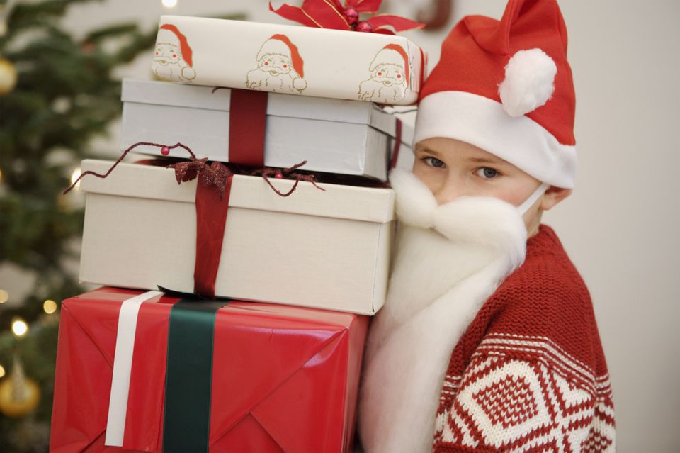 A boy dressed as Santa holding a stack of gifts.