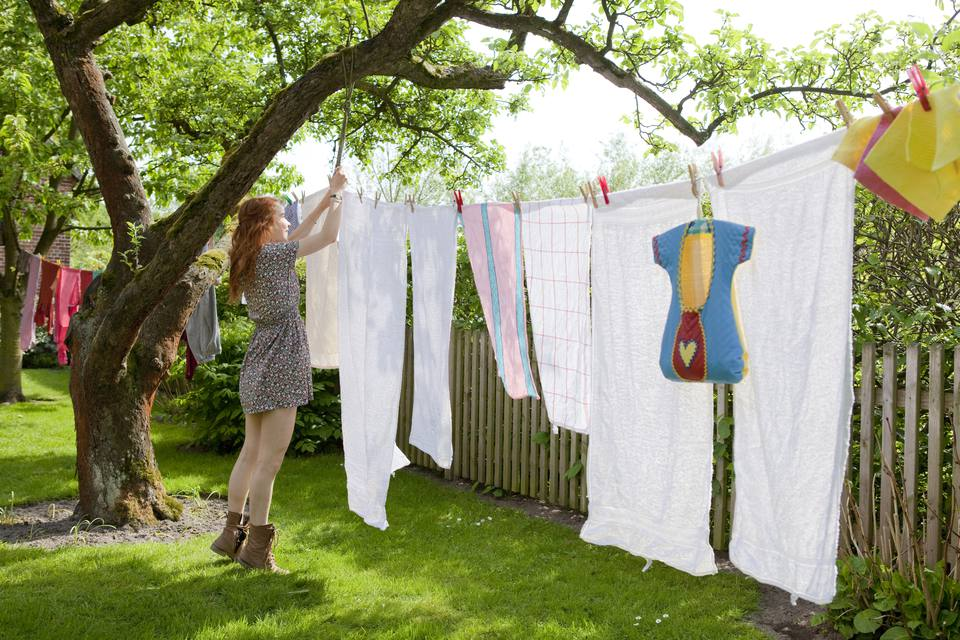 Girl hanging laundry on a garden clothesline